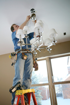 certified-electrician-installing-chandelier