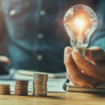 man-at-table-holding-lit-light-bulb-by-stacks-coins-energy-efficient-home-upgrades-colvin-electric